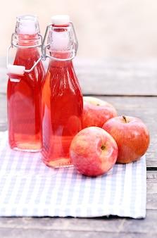 Bouteilles avec des boissons rouges et des pommes