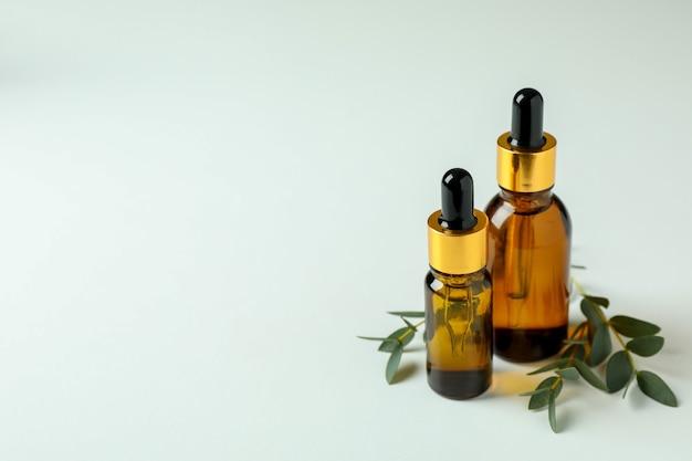 Bouteilles brunes d'huile d'eucalyptus et de brindilles sur fond blanc