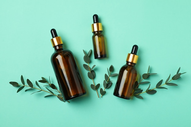Bouteilles brunes d'huile d'eucalyptus et de brindilles sur fond de menthe