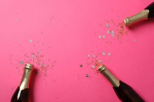 Bouteilles de champagne et paillettes sur rose, espace pour le texte