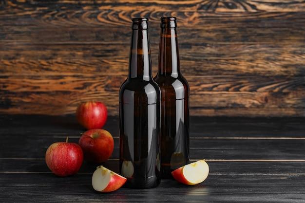 Bouteilles de cidre de pomme sur bois