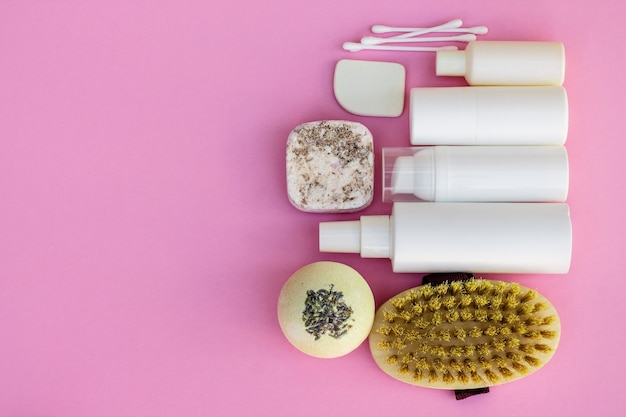 Bouteilles cosmétiques blanches, bombe de bain, savon artisanal, sel de bain, brosse de massage, éponge, cotons-tiges avec fleurs de cerisier sur fond rose. concept de cosmétiques biologiques naturels.