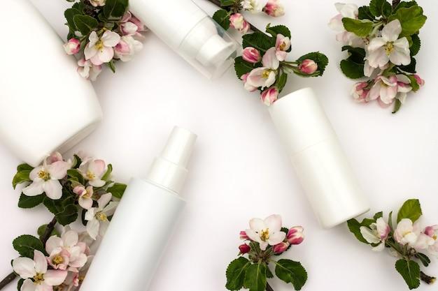 Bouteilles cosmétiques blanches avec des fleurs de poire sur fond blanc. concept de cosmétiques biologiques naturels.