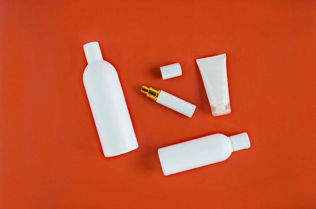 Bouteilles cosmétiques blanches sur fond rouge avec plase pour le texte. vue de dessus, mise à plat. spa, soins de la peau, soins du corps, du visage et des cheveux.