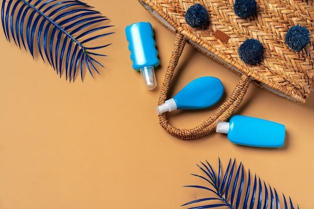 Bouteilles cosmétiques bleues sur fond beige avec des feuilles de palmier tropical bleu