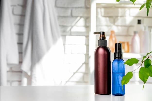 Bouteilles cosmétiques sur fond de mur de salle de bain blanc