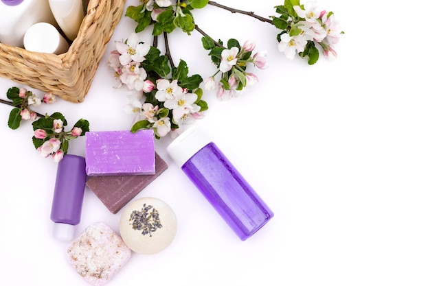Bouteilles cosmétiques lilas, bombe de bain, savon artisanal, sel de bain près d'un panier en osier avec des fleurs de poire sur fond blanc. concept de cosmétiques biologiques naturels. mise à plat