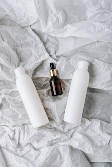 Bouteilles de cosmétiques sur papier froissé blanc