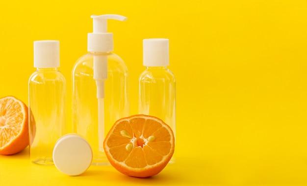 Bouteilles cosmétiques transparentes en plastique avec bouchon blanc et citrons sur jaune