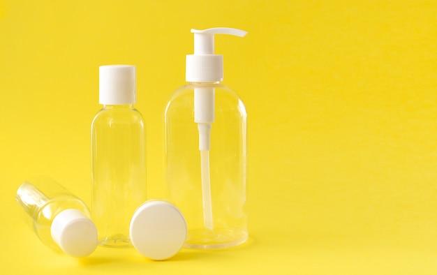 Bouteilles cosmétiques transparentes en plastique avec un couvercle blanc sur fond jaune