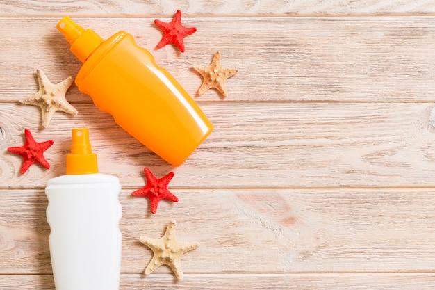 Bouteilles de crème solaire avec des coquillages et des étoiles de mer sur une table en bois avec espace de copie. concept plat de vacances de voyage d'été