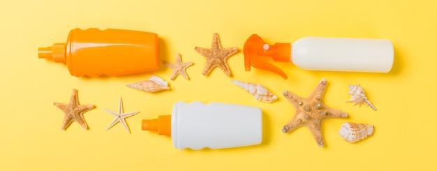 Bouteilles de crème solaire avec coquillages sur la vue de dessus de table jaune
