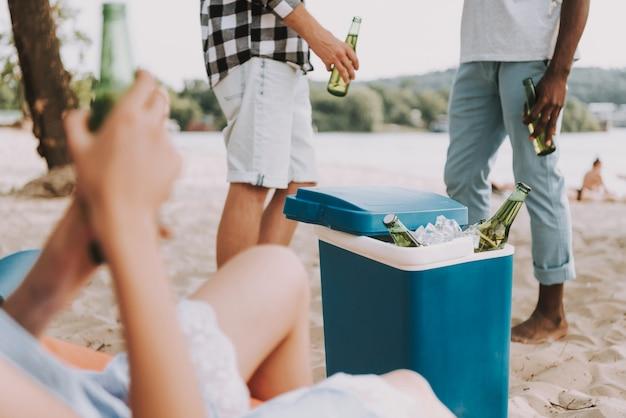 Bouteilles dans un réfrigérateur portatif à la fête sur la plage