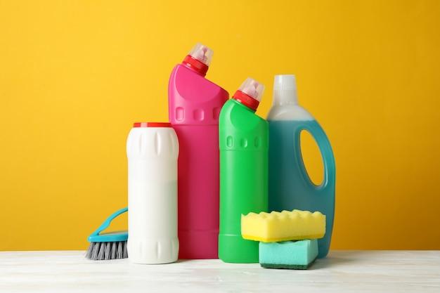 Bouteilles de détergent et de produits de nettoyage sur jaune, espace pour le texte