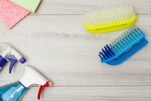 Bouteilles de détergent, serviettes en microfibre de couleur et brosse pour le nettoyage sur fond de bois gris avec espace de copie au centre. ensemble d'outils et d'équipements de nettoyage