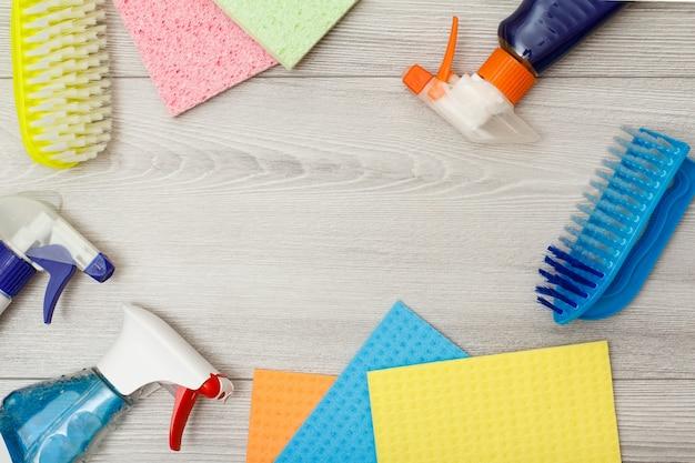 Bouteilles de détergent, serviettes en microfibre de couleur et brosse synthétique pour le nettoyage sur fond de bois gris avec espace de copie au centre. ensemble d'outils et d'équipements de nettoyage