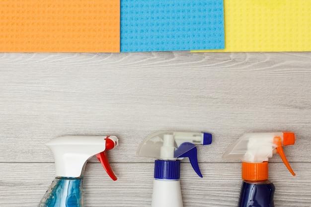 Bouteilles de détergent et serviettes en microfibre de couleur pour le nettoyage sur fond de bois gris avec espace de copie au centre. ensemble d'outils et d'équipements de nettoyage