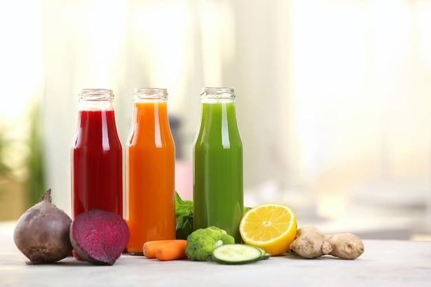 Bouteilles avec divers jus de légumes frais sur table