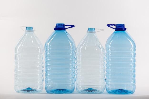 Des bouteilles d'eau claire de plus grande taille se tenant dans la rangée de droite comme exemple de gaspillage supplémentaire