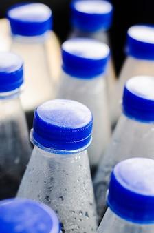 Bouteilles d'eau avec des tasses bleues