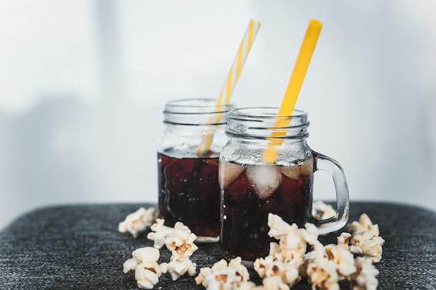 Bouteilles embuées de cola avec glace et maïs à la marmite fraîche