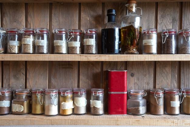 Bouteilles d'épices et d'assaisonnements dans une grille en bois. diverses herbes biologiques différentes.