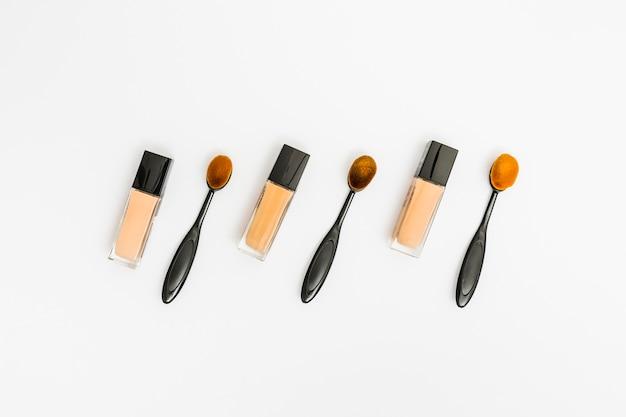 Bouteilles fermées de teint liquide avec un pinceau de maquillage ovale sur fond blanc