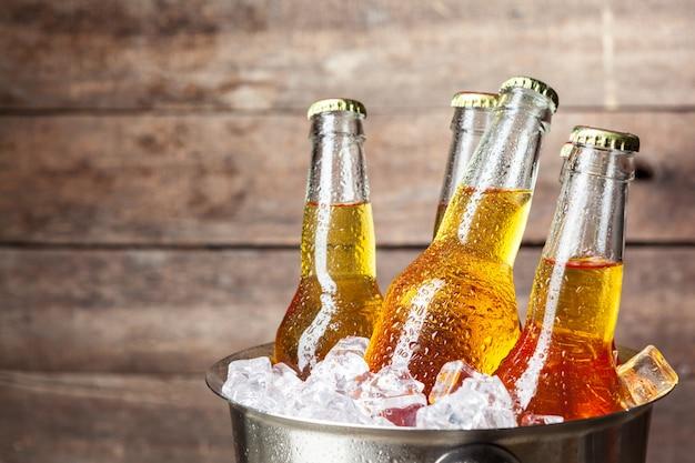 Bouteilles froides de bière dans le seau sur bois
