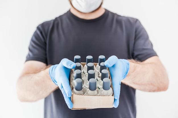 Bouteilles de gel d'alcool d'hygiène désinfectant pour les mains dans les mains de l'homme