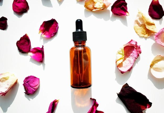 Bouteilles d'huile aromatique aux pétales de rose. les bases de l'aromathérapie. vue de dessus. soins botaniques pour la peau soins à domicile.