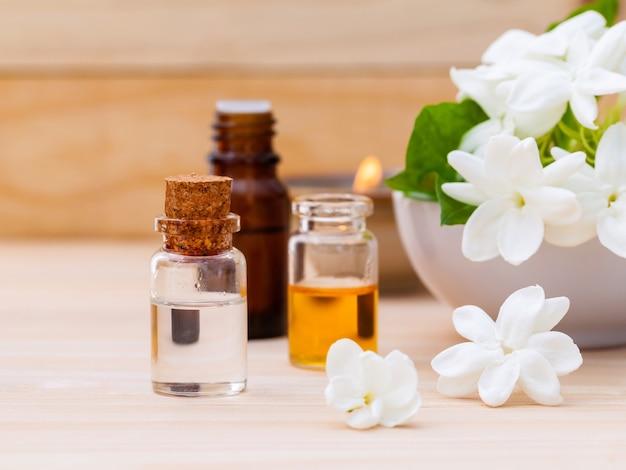 Bouteilles d'huile aromatique disposées avec des fleurs de jasmin sur fond de bois.