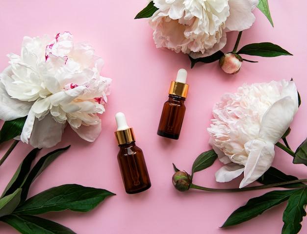 Bouteilles d'huile aromatique en verre et fleurs de pivoine sur pastel rose.