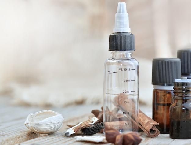 Bouteilles d'huile essentielle et bouteille graduée vide avec des épices sur une table en bois