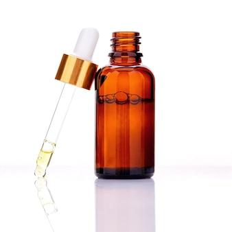 Bouteilles d'huile essentielle avec compte-gouttes et bulle isolé sur blanc.
