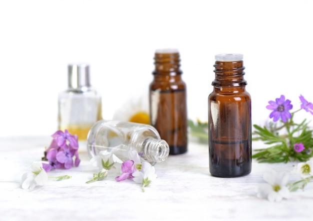 Bouteilles d'huile essentielle et pétales de fleurs colorées sur tableau blanc