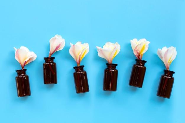 Bouteilles d'huile essentielle avec plumeria ou fleur de frangipanier sur une surface bleue