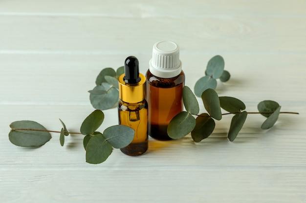 Bouteilles d'huile d'eucalyptus et brindilles sur fond de bois blanc