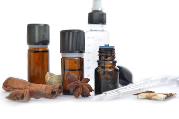 Bouteilles d'huiles essentielles et de cannelle et d'anis sur fond blanc