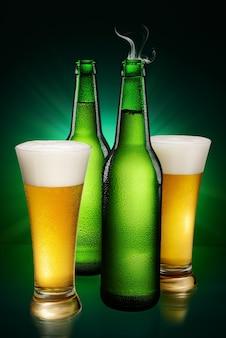 Bouteilles humides vertes et verres de bière sur fond vert.