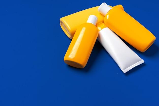 Bouteilles jaune vif de produit de protection solaire sur fond de papier bleu foncé