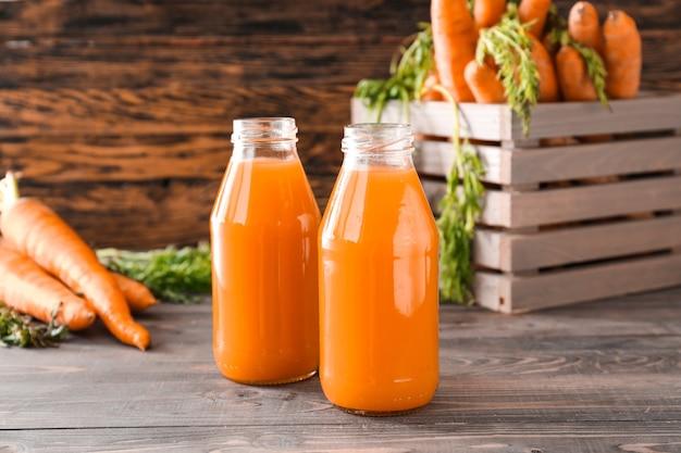 Bouteilles de jus de carotte savoureux sur table en bois