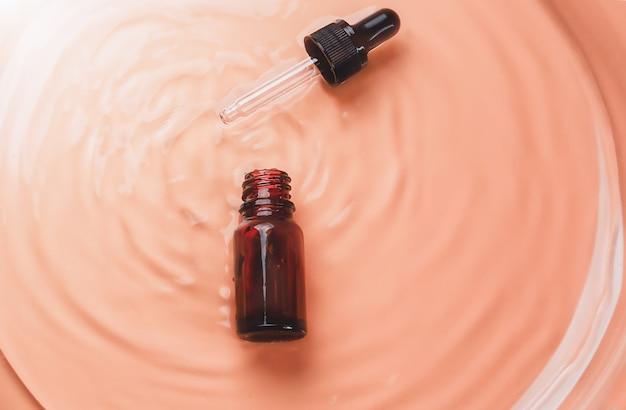 Bouteilles de laboratoire cosmétique abstraites de verre ambré foncé sur fond liquide beige cosmétique naturelle...