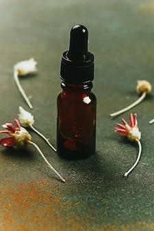 Bouteilles de laboratoire cosmétique abstraites de verre ambré foncé sur fond de podium vert cosmétique naturelle...