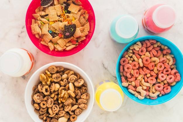 Bouteilles de lait debout avec des bols de céréales sur la table