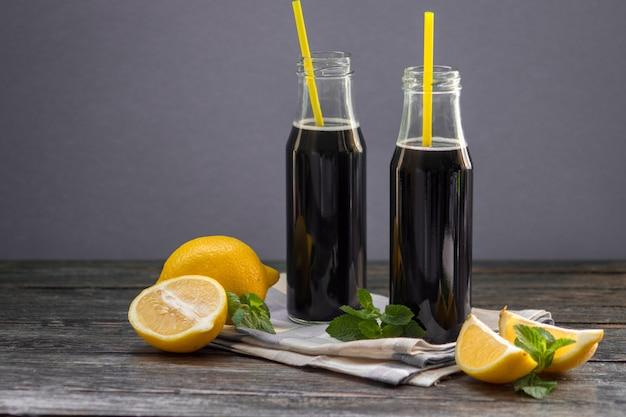 Bouteilles avec de la limonade noire au charbon activé détox sur table