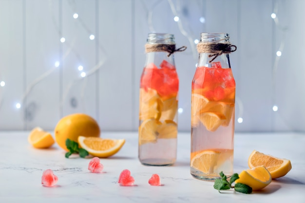 Bouteilles avec de la limonade rafraîchissante et des glaçons en forme de coeur sur une table en marbre. boisson saint valentin