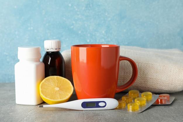 Bouteilles médicales, pilules, citron et thermomètre sur table grise, espace pour le texte