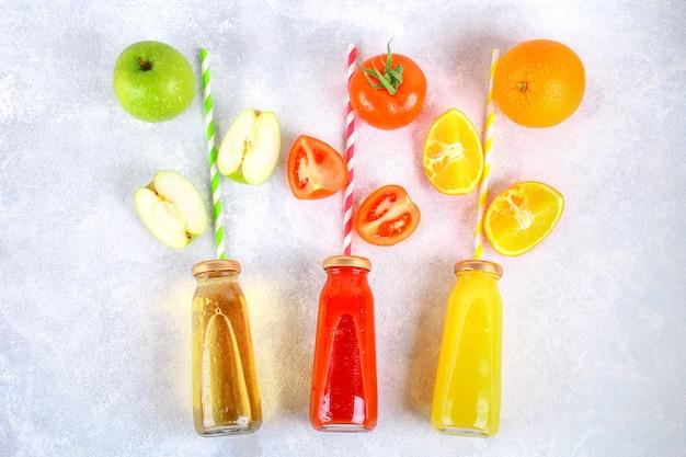 Bouteilles avec orange fraîche, pomme, jus de tomate et tubules colorés sur une table en béton grise.