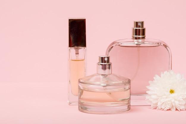 Bouteilles avec parfum féminin et bouton floral sur fond rose avec espace de copie. produits pour femmes.