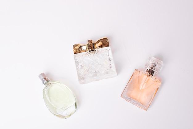 Bouteilles de parfum féminin sur fond blanc